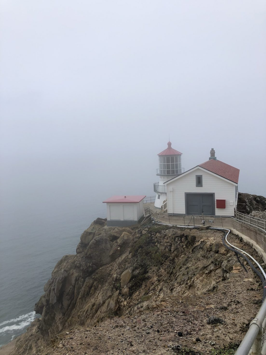 Rocky cliff in foreground, small lighthouse and neighboring white structures with red roofs in midground, and fog visible in background.