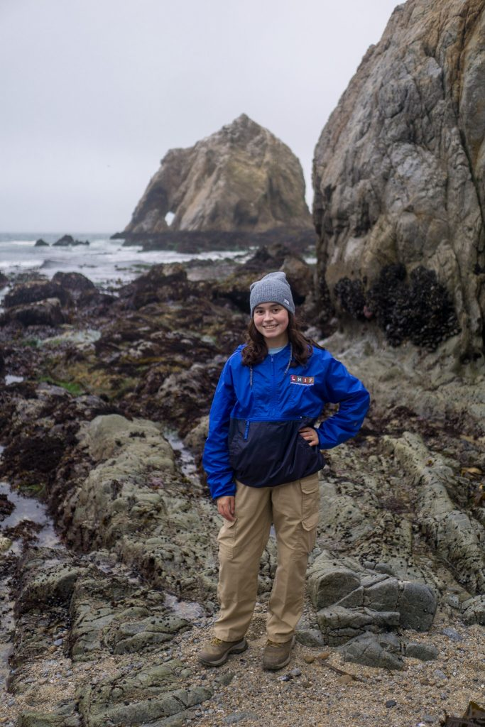 Young Latina woman is posing to the camera in her uniform. There is a grey rocky ground, a boulder on the right, and a large rock in the water in the background called Elephant rock.