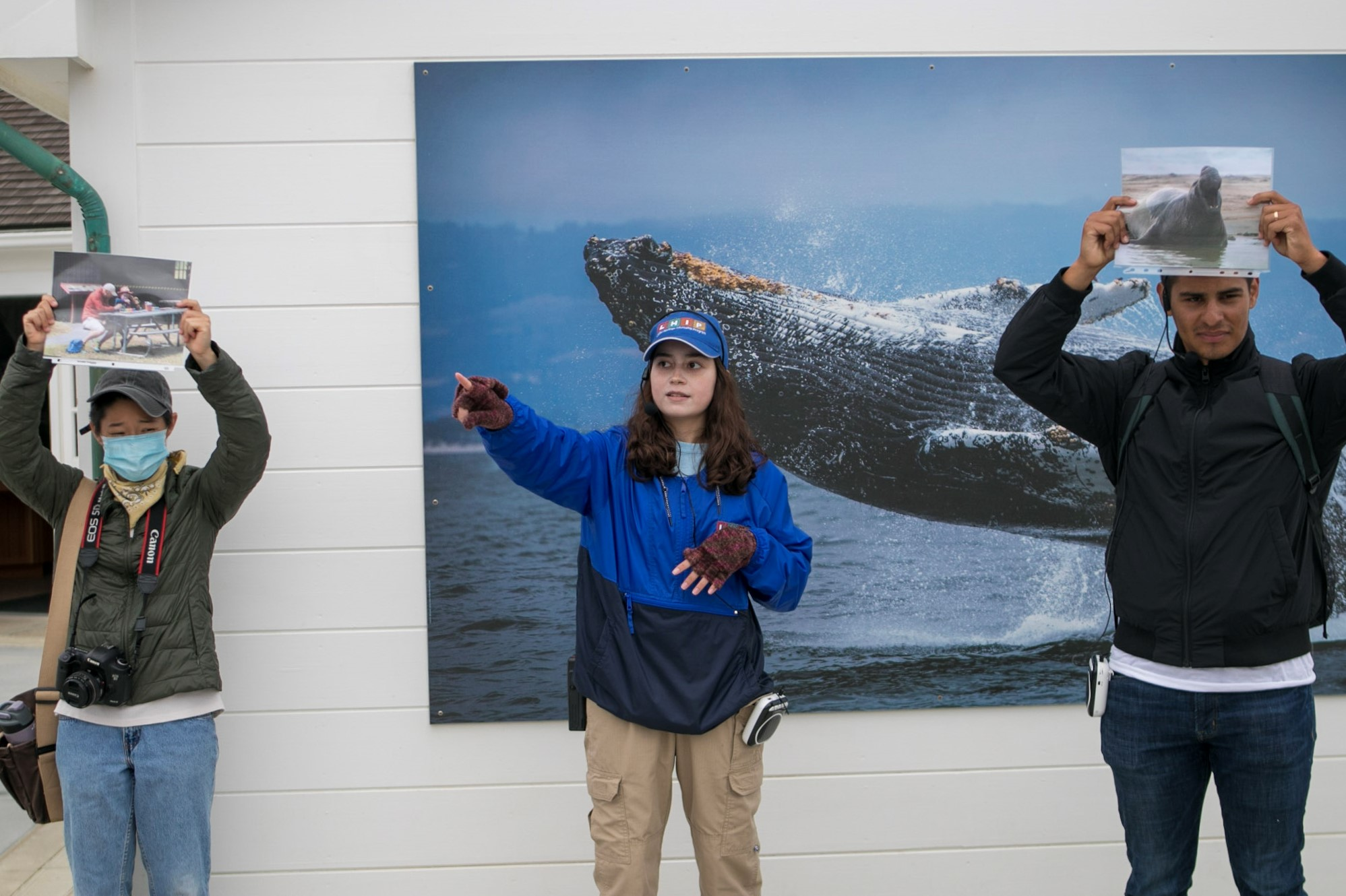 Woman in LHIP uniform is pointing to the distance at the center of the image. Two people are on either side of her holding up printed images. There is an image of a whale on the wall in the background.