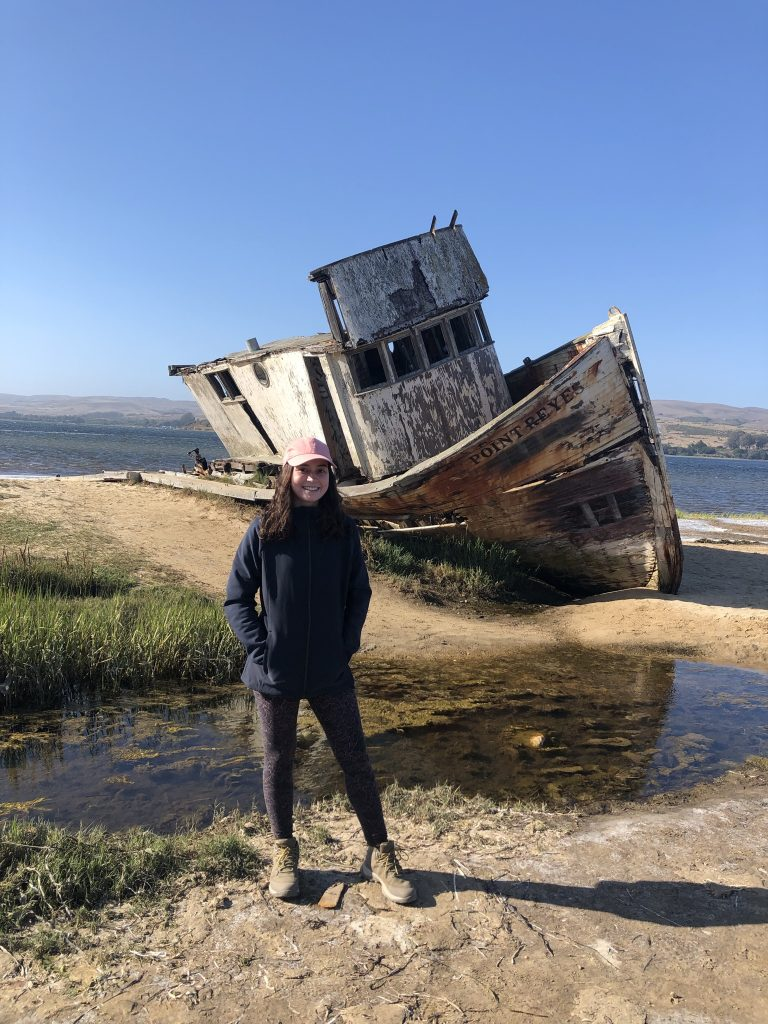 """Woman is posing in front of an old boat that says """"Point Reyes"""" on the side."""